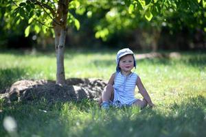 lindo menino no jardim infantil posando fotógrafo foto