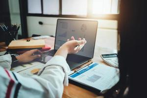 focus women holding pen, uma consultora de negócios descreve um plano de marketing para definir estratégias de negócios para mulheres empresárias. foto