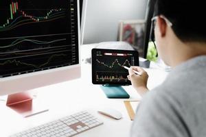 profissionais de investimento apontam sua caneta para o monitor do computador para analisar o mercado de ações para obter lucro. foto
