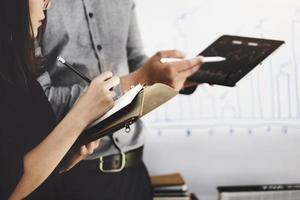 mulher usando caneta para anotações com um especialista em investimentos aponta uma caneta para um monitor de tablet para analisar o mercado de ações e ensiná-lo a ter lucro. foto