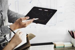 um especialista em investimentos aponta uma caneta para um monitor de tablet para analisar o mercado de ações e ensiná-lo a obter lucro. foto