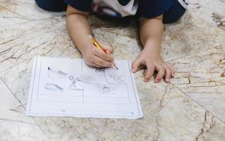 infância aprendendo a usar o lápis para desenhar e escrever no papel. foto