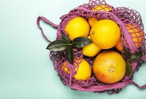 sacola de compras de malha com laranjas foto