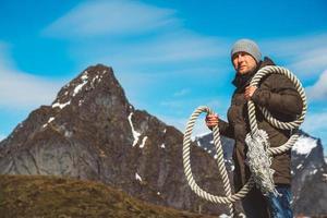 homem com uma corda no ombro contra o fundo das montanhas e do céu azul foto