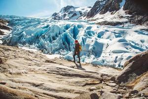 homem viajante de pé sobre uma rocha no fundo de uma geleira, montanhas e neve foto