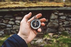 bela mão masculina segura uma bússola magnética contra o fundo de rochas de uma casa e uma montanha foto