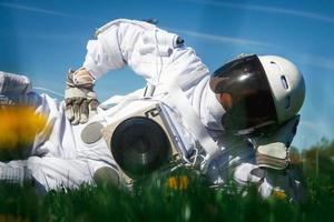 astronauta futurista em um capacete em um gramado verde foto
