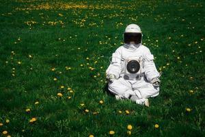 astronauta futurista com um capacete sentado em um gramado verde em posição meditativa foto