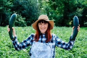 agricultora segura uma abobrinha em sua horta foto