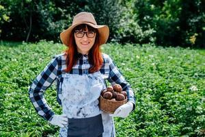 agricultora segura uma batata em uma cesta de vime usando um chapéu de palha e cercada por muitas plantas em sua horta foto