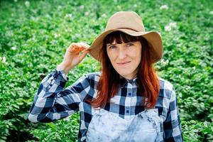 retrato mulher agricultora sorrindo para a câmera usando um chapéu de palha em sua horta foto