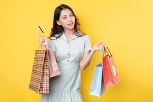 jovem empresária asiática segurando sacolas de compras, posando em fundo amarelo foto