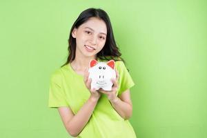 menina asiática segurando o cofrinho na mão conceito de economia de dinheiro foto
