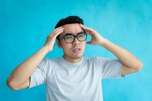 retrato de homem com dor de cabeça, isolado em fundo azul foto