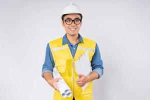 sorridente jovem engenheiro civil asiático usando capacete de proteção em pé sobre fundo branco isolado. conceito de serviço mecânico. foto