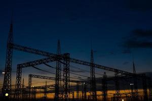 sol se pondo sobre uma subestação elétrica. foto