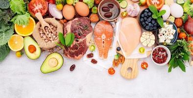 conceito de dieta de baixo teor de carboidratos cetogênica. ingredientes para seleção de alimentos saudáveis configurados em fundo branco de concreto foto