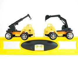 carro de guindaste de brinquedo e escavadeira mecânica com nível de construção em fundo branco, conceito de construção de engenharia foto
