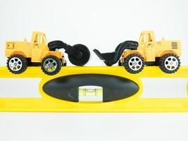 carro de estrada de pressão de brinquedo e escavadeira com nível de construção em fundo branco, conceito de construção de engenharia foto