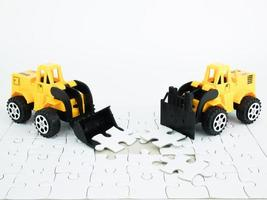 escavadeira e empilhadeira de brinquedo com quebra-cabeça no fundo branco foto