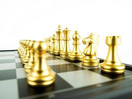 figuras de xadrez de ouro a bordo para o início do jogo, esporte intelectual e jogo tático foto