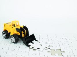 trator de brinquedo com quebra-cabeça no fundo branco foto