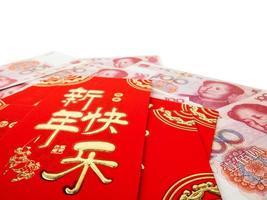 envelopes vermelhos chineses sobre dinheiro chinês pilha de notas de cem yuans, isolada no fundo branco. texto chinês no envelope significa feliz ano novo chinês foto