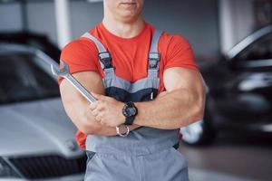 mãos do mecânico de automóveis com a chave inglesa na garagem foto