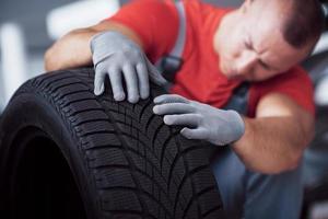mecânico segurando um pneu na oficina. substituição de pneus de inverno e verão foto