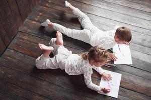crianças deitam-se no chão de pijama e desenham a lápis. criança fofa pintando a lápis foto