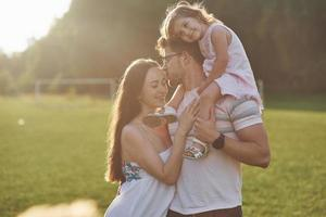 mãe e pai passam tempo juntos felizes. filha brinca com os pais ao ar livre durante o pôr do sol foto