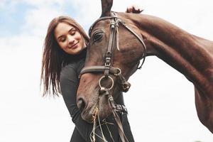 uma garota feliz se comunica com seu cavalo favorito. a menina adora animais e passeios a cavalo foto