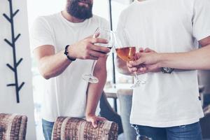 velhos amigos alegres se comunicam uns com os outros em copos de uísque no bar. conceito de entretenimento e estilo de vida foto