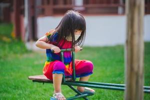 criança usando máscara está brincando com cavalo abatido. garota jogava equipamentos de playground. prevenir a propagação de coronavírus e poeira pm2.5 pela poluição do ar. crianças se exercitam. momento relaxante para uma criança de 4 anos. foto