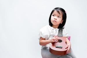 adorável criança menina coloca seu ukulele no ombro. criança toca instrumentos musicais, olhando para os lados. em fundo branco do estúdio. foto