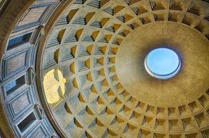 panteão romano de dentro com céu azul e reflexo do sol no buraco da cúpula foto