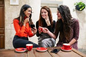 grupo de três amigos felizes bebendo café em um café-bar. foto
