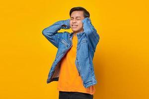 retrato de homem asiático com raiva cobrindo os ouvidos com as mãos foto