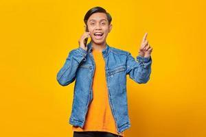 jovem asiático chocado enquanto fala no smartphone e dedo apontando para cima. fundo amarelo foto