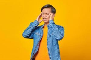 jovem asiático sentindo dor de cabeça em fundo amarelo foto