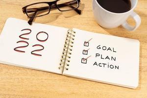 objetivo de ano novo 2022, plano, texto de ação no bloco de notas na mesa de madeira. conceito de lista de verificação motivacional foto