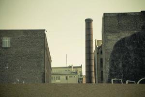 prédio de fábrica antiga com chaminé de tijolos industriais foto