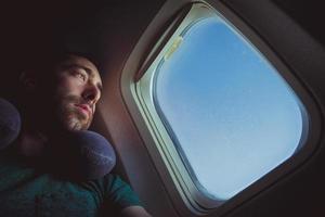 homem pensativo com almofada no pescoço, olhando para fora pela janela de um avião foto