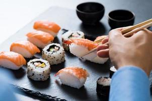 homem comendo sushi foto