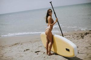 mulheres jovens com prancha de remo na praia em um dia de verão foto