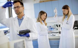 pesquisadoras em jaleco branco trabalhando no laboratório foto