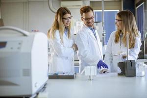 pesquisadores em roupas de trabalho de proteção em pé no laboratório e analisando amostras de líquidos em equipamentos de cromatografia de íons foto