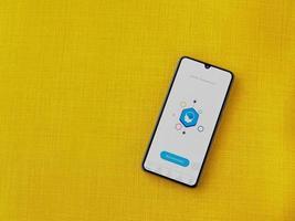 elevar - tela inicial do aplicativo de jogos de treinamento cerebral com logotipo na tela de um smartphone móvel preto em um fundo de tecido amarelo foto