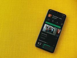 caderno de esboços da autodesk - desenhe e pinte a página da app play store na tela de um smartphone móvel preto em um fundo de tecido amarelo foto
