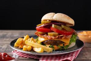 hambúrguer de carne com queijo, bacon e batata frita foto